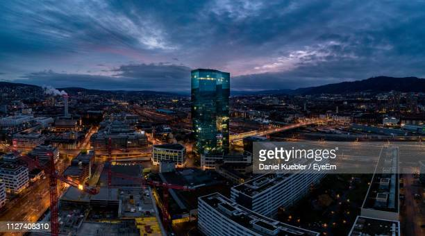 high angle view of illuminated city buildings at night - zürich stock-fotos und bilder