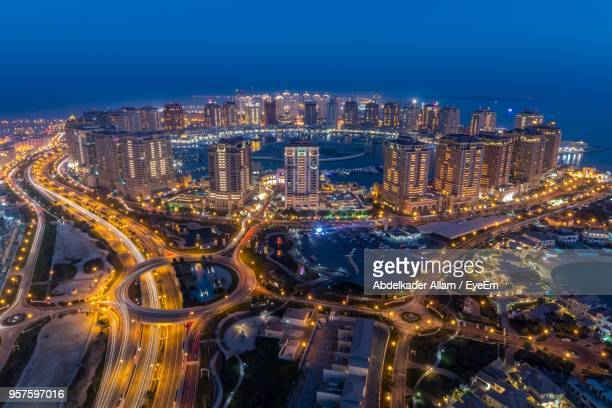 high angle view of illuminated city buildings at night - doha stock pictures, royalty-free photos & images