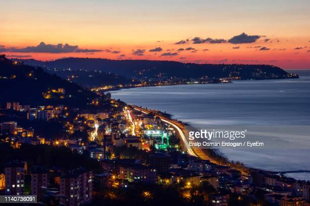 high angle view of illuminated city by buildings against sky during sunset - trabzon stock pictures, royalty-free photos & images
