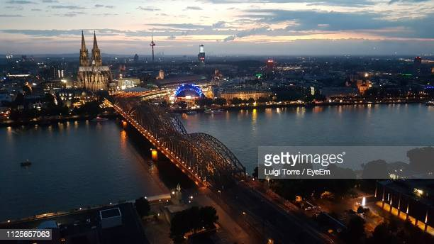 high angle view of illuminated city by river against sky - cologne cathedral stock photos and pictures