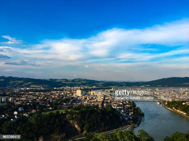 high angle view of illuminated city by river against sky - linz stock pictures, royalty-free photos & images
