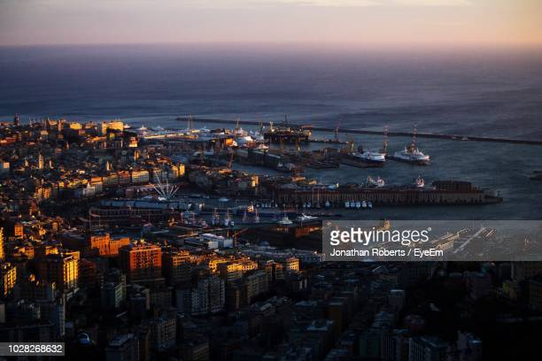 high angle view of illuminated city by sea against sky - genoa italy stock pictures, royalty-free photos & images