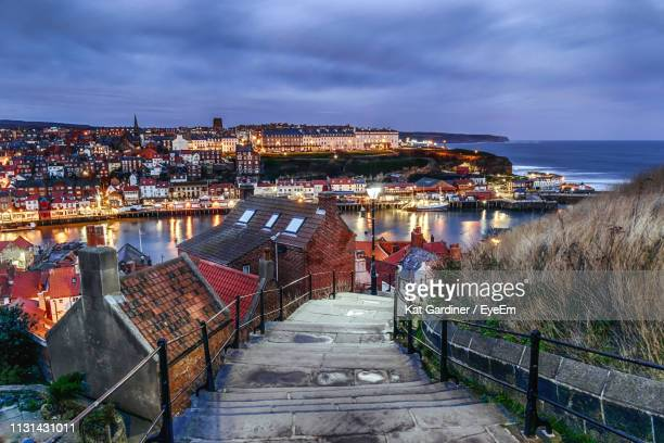 high angle view of illuminated city by sea against sky - whitby north yorkshire england stock photos and pictures