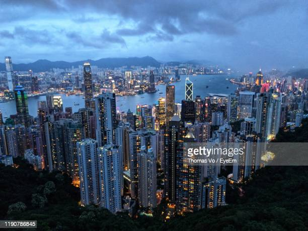 high angle view of illuminated city by sea against sky - stock exchange stock-fotos und bilder