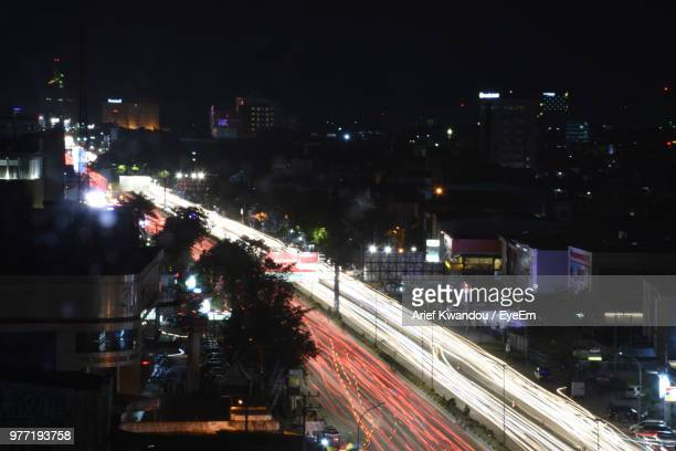 high angle view of illuminated city street and buildings at night - makassar stock pictures, royalty-free photos & images