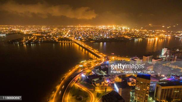 high angle view of illuminated city with river at night - côte d'ivoire stock pictures, royalty-free photos & images