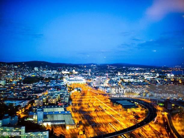 High Angle View Of Illuminated Cityscape Against Blue Sky