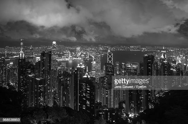 High Angle View Of Illuminated Cityscape Against Cloudy Sky