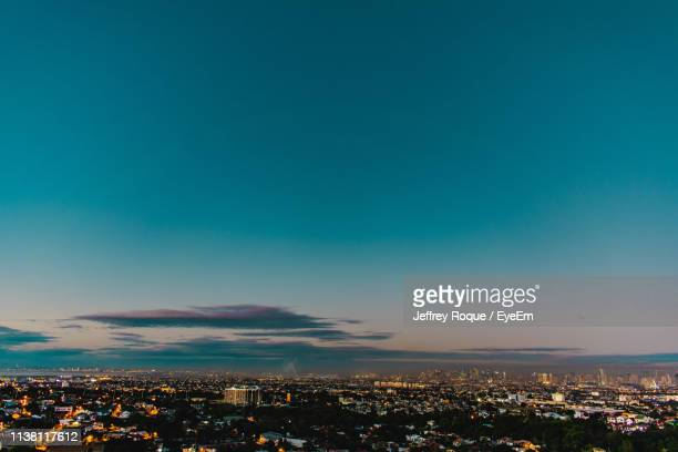 high angle view of illuminated cityscape against sky at night - jeffrey roque stock photos and pictures