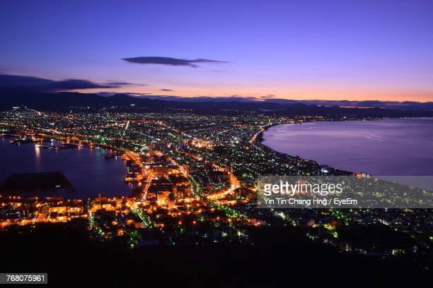 high angle view of illuminated cityscape against sky at sunset - hokkaido stock pictures, royalty-free photos & images