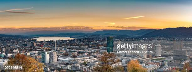 high angle view of illuminated cityscape against sky during sunset - zürich stock-fotos und bilder