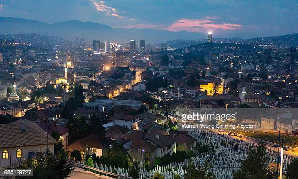 high angle view of illuminated cityscape sunset - sarajevo stock-fotos und bilder