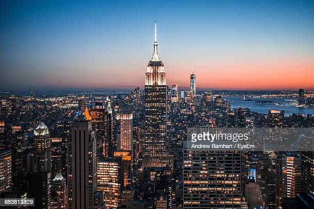 high angle view of illuminated empire state building and city against clear blue sky at night - empire state building stock pictures, royalty-free photos & images