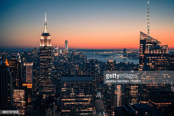 high angle view of illuminated empire state building and cityscape against clear sky at night - new york state fotografías e imágenes de stock