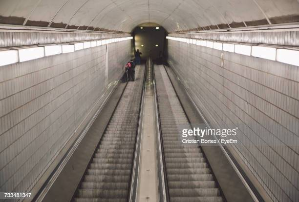 high angle view of illuminated escalator in subway station - bortes stock-fotos und bilder