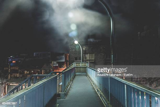 high angle view of illuminated footbridge in city at night - footbridge stock photos and pictures