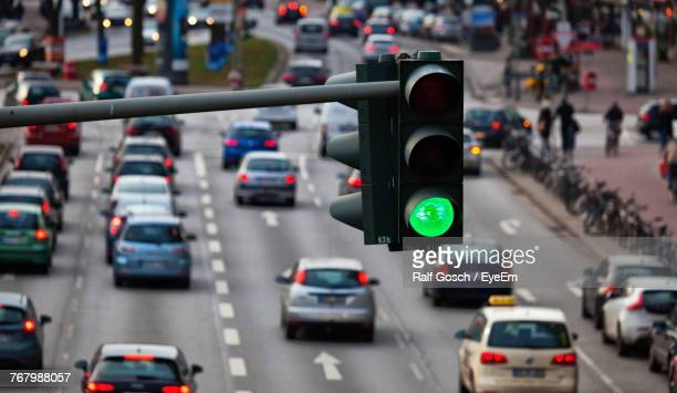High Angle View Of Illuminated Green Light Against Cars On Street