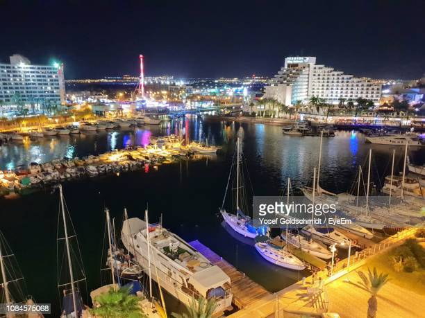 high angle view of illuminated harbor by buildings in city at night - eilat stock pictures, royalty-free photos & images