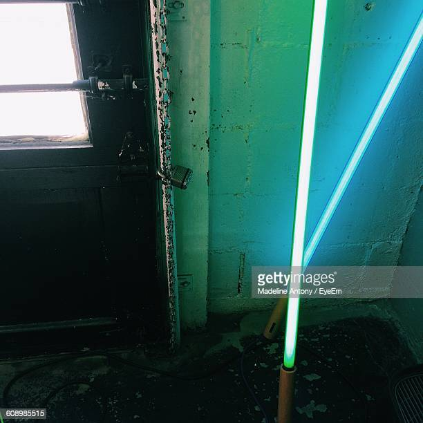 High Angle View Of Illuminated Laser Swords On Floor Against Closed Door