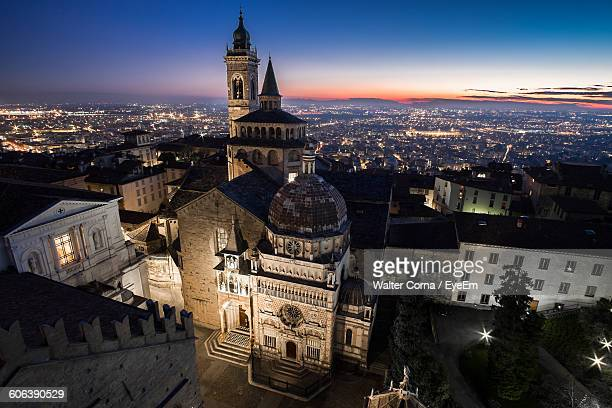 high angle view of illuminated residential district at dusk - bergamo alta foto e immagini stock