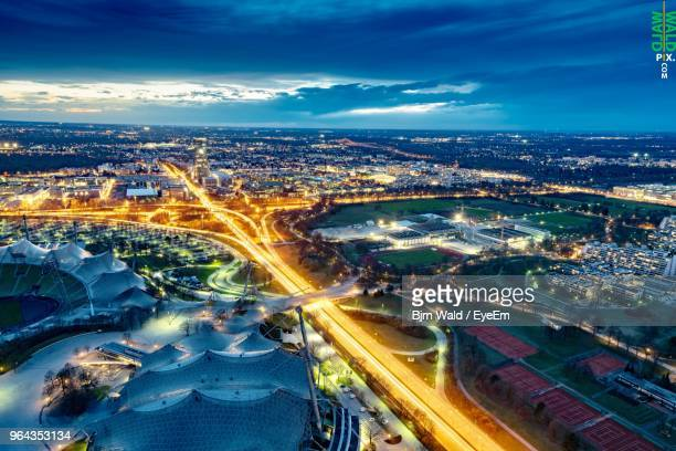 high angle view of illuminated street amidst buildings in city at night - münchen stock-fotos und bilder
