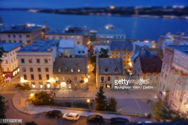 high angle view of illuminated street amidst buildings in city - old quebec stock pictures, royalty-free photos & images