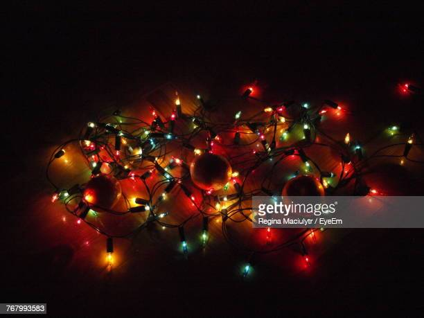 High Angle View Of Illuminated String Lights With Baubles On Table