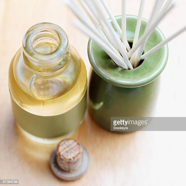high angle view of incense sticks in burner with bottle of oil - hob stock photos and pictures