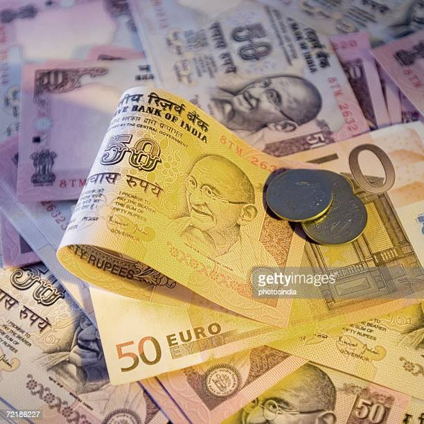 High angle view of Indian banknotes and coins with a fifty Euro banknote