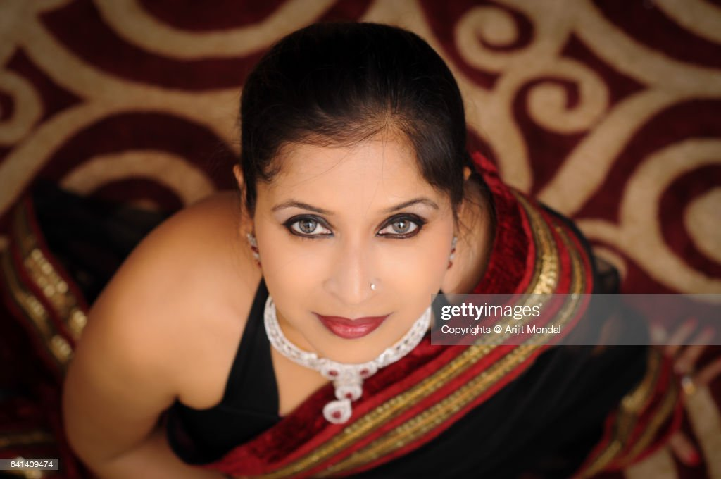 High angle view of Indian woman looking at camera in black sari with diamond necklace : Stock Photo