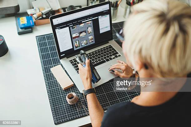 High angle view of industrial designer using laptop while holding product at home office