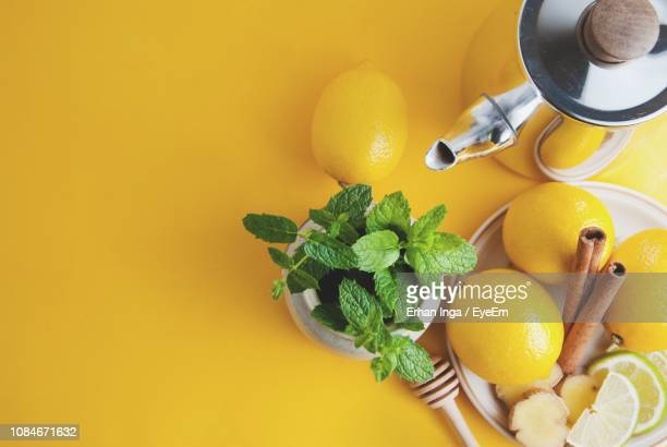 high angle view of ingredients with kettle over yellow background - ginger plant stock pictures, royalty-free photos & images