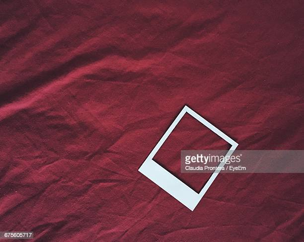 High Angle View Of Instant Print Transfer On Maroon Sheet