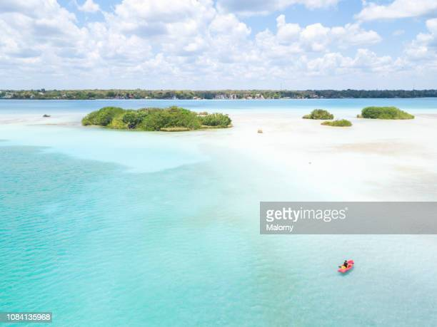 high angle view of island, turquoise ocean and young woman paddling in a canoe. - hot women on boats stock pictures, royalty-free photos & images