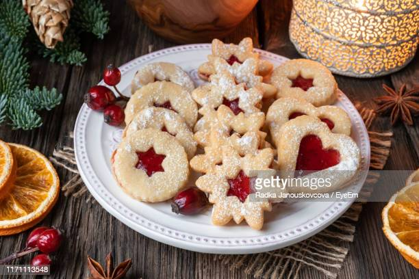 high angle view of jam cookies with christmas decorations on wooden table - spread food stock pictures, royalty-free photos & images