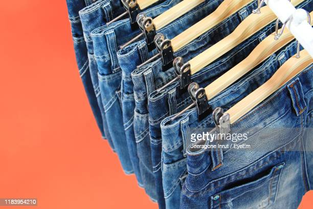 high angle view of jeans over orange background - dress over pants stock pictures, royalty-free photos & images