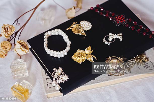 High Angle View Of Jewelries On Book