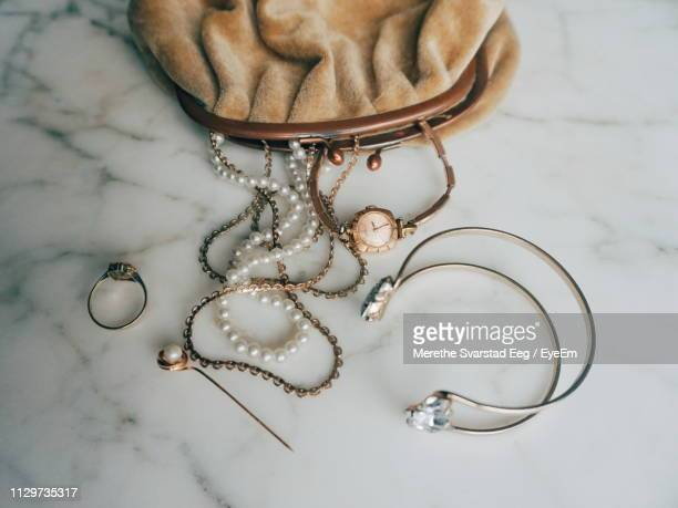 high angle view of jewelry by purse on table - diamond necklace stock pictures, royalty-free photos & images