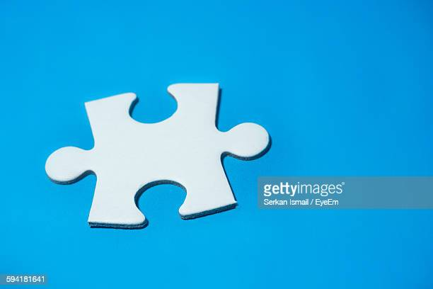 High Angle View Of Jigsaw Piece Against Blue Background