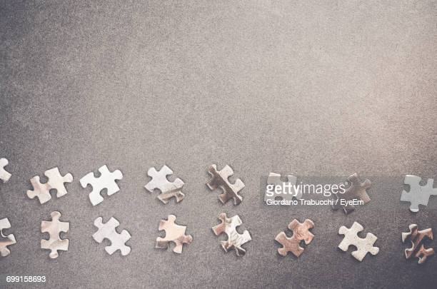 High Angle View Of Jigsaw Pieces Arranged On Slate Board