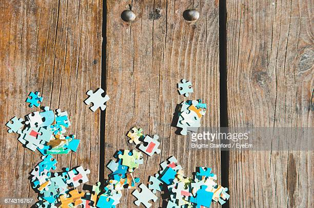 High Angle View Of Jigsaw Pieces On Wooden Table