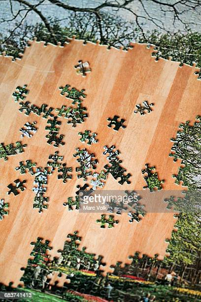High angle view of jigsaw puzzle with shattered pieces on wooden table
