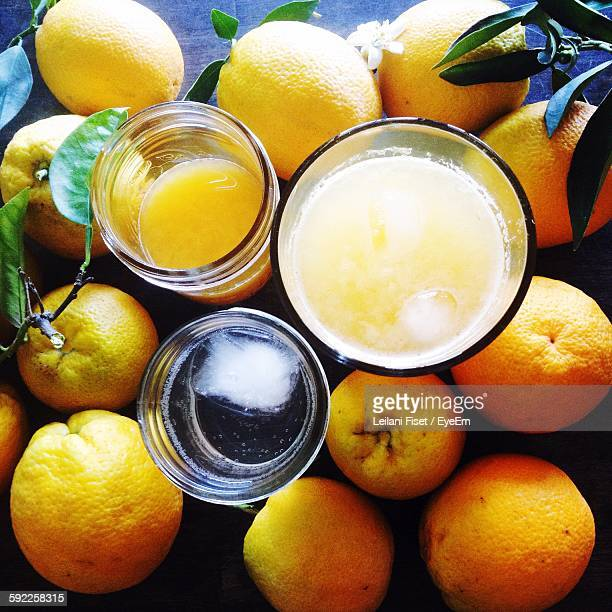 High Angle View Of Juices Amidst Oranges On Table