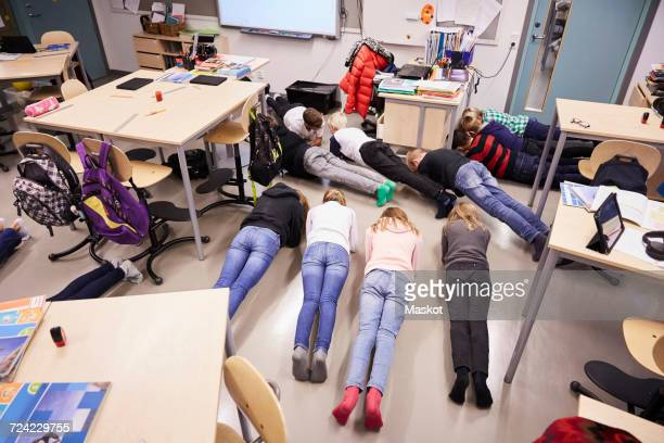 High angle view of junior high students in plank position at classroom