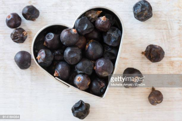 High Angle View Of Juniper Berries In Heart Shape Pastry Cutter On Table