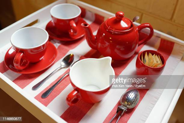 high angle view of kettle with tea cups in tray on table - red kettle stock photos and pictures