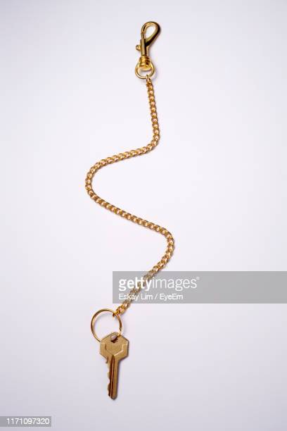 high angle view of key in ring with chain against white background - chain stock pictures, royalty-free photos & images