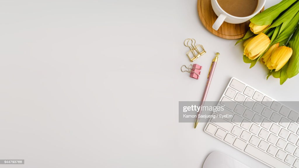 High Angle View Of Keyboard With Tulips And Coffee On Table : Stock Photo