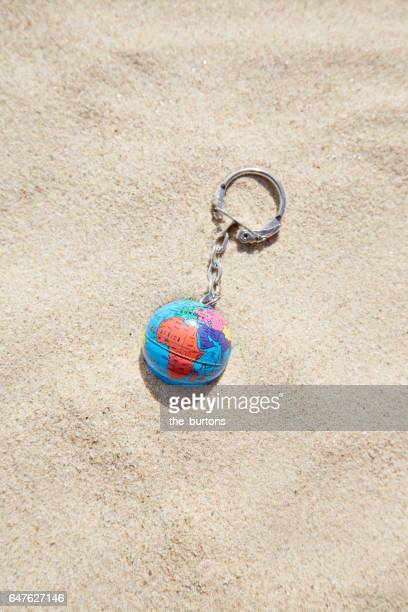 High angle view of keychain with globe on the beach