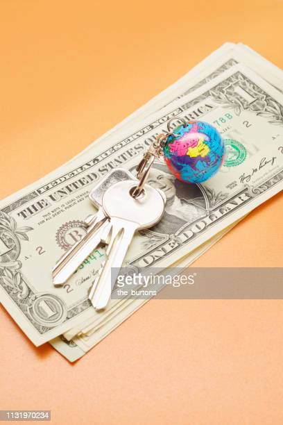 High angle view of keyring with a small globe and American Dollar banknotes on colored background